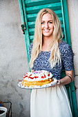 Smiling blonde woman holding cake