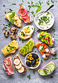 Assorted healthy ciabatta sandwiches with dips, fish, cheese, meat, vegetables, fruits