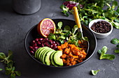 Quinoa salad in bowl with avocado, sweet potato, beans, herbs, orange on concrete rustic background