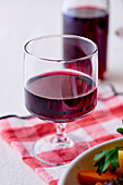 A glass of red wine on a checkered napkin