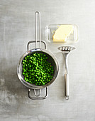 Peas in a metal sieve with butter