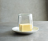 Butter being covered with a hot glass to soften it