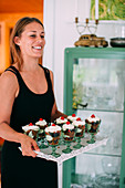 Woman holding tray with desserts