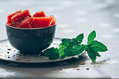 Watermelon in bowl garnished with mint leaves