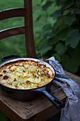 Kartoffelgratin in Pfanne auf Holzstuhl