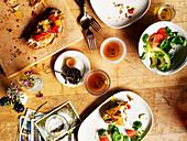 Tischszene mit halb gegessenen Brötchen, Salat und Gewürztee
