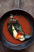 Chile Relleno with red salsa in cast iron skillet