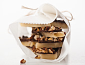 Toffee with chocolate and nuts, stacked and wrapped in parchment