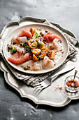 Fish carpaccio with marinated tomatoes and red salt
