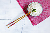 Boiled jasmine rice in a bowl with chopsticks