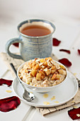 Apple cinnamon porridge with almond flakes and cup of tea