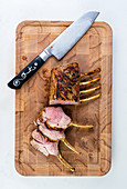 Rack of lamb on a cutting board with a knife