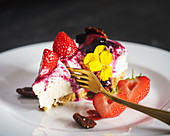 Summer cheescake, slice with berry compote and strawberries