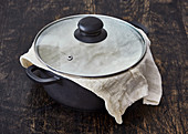 Rice in a pot covered with a cloth and a lid