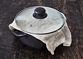 Reis im Topf bedeckt mit Tuch und Deckel