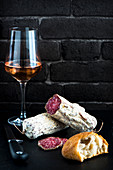A glass of rose wine with salami and bread