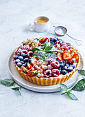 Berry tart with powdered sugar and fresh mint