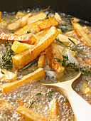 Tuscan fries with garlic, thyme and rosemary in frying oil