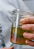 Vinaigrette sauce in a glass jar (close-up)