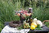 Herbst-Arrangement mit Kürbissen, Birnen und Gesteck auf dem Gartentisch