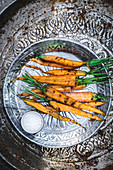Grilled carrots on metal plate