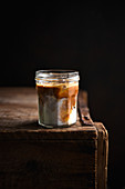Dark Iced Latte in a jar on a wooden table