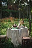 Gedeckter Kaffeetisch mit Bundt Cake auf sommerlicher Waldwiese