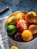 Zitrusfrüchte in Schüssel, teilweise geschält