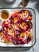 Radicchio salad with rainbow carrots, berries, fruits and hazelnuts served in white tray