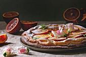 Flacher Käsekuchen mit sizilianischen Blutorangen dekoriert mit Essblüten