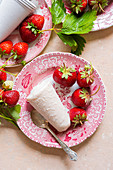 Strawberry Kulfi served on pink china plates, pink linen with fresh picked strawberries