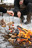 Two people cooking skewers by campfire
