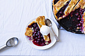 Cherry pie with a lattice and flaky crust shot on a white fabric served with vanilla ice cream