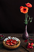 Mini-Erdbeertarte auf Holztisch daneben Mohnblume in Vase