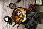 Fresh baked Dutch baby pancake in iron cast pan served with blackberry and red currant berries, mascarpone cheese, sugar powder, jug of cream
