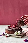 Veganen Schokoladen-Himbeerkuchen anschneiden