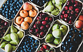 Summer fruit and berry variety: Flat-lay of ripe strawberries, cherries, grapes, blueberries, pears, apricots, figs in wooden eco-friendly boxes