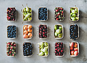 Summer fruit, berry assortment: Flat-lay of fresh strawberries, cherries, grape, blueberries, pears, apricots, figs in eco-friendly boxes