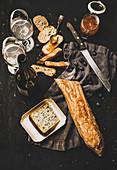 Baguettebrot, Käse, Marmelade und Wein auf dunklem Untergrund