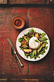 Flat-lay of seasonal salad with Burrata soft cheese and grilled peaches with glass of rose wine