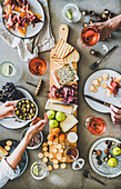 Charcuterie and cheese board, rose wine, nuts, olives and peoples hands holding glasses and food