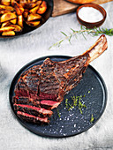 Sliced medium rare grilled angus beef tomahawk steak on a dark plate with roasted potatoes in wrought iron pan