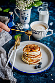 Blueberry pancakes stack with honey, coffee with milk in the background