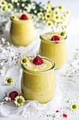 Kokos-Ananas-Tapioka-Dessert in Gläsern mit Himbeeren und Kokosflocken