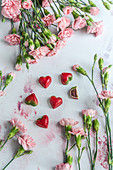 Chocolate-strawberry heart-shaped pralines with pink flowers