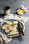 Pierogi dumplings with pumpkin and rosemary served on a ceramic dark plate