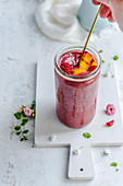Raspberry-mango smoothie in a jar