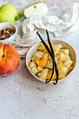 Apples stewed with peaches and vanilla in a bowl