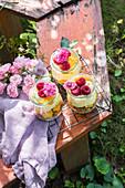 Sommerdessert aus Keksen, Pfirsich, Vanillecreme und Himbeeren im Glas auf Gartentisch