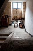 Steinguttöpfe, Stuhl und Schränkchen auf dem Absatz einer alten Steintreppe